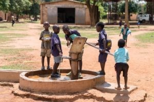 Kinder trinken Wasser aus einem Brunnen.