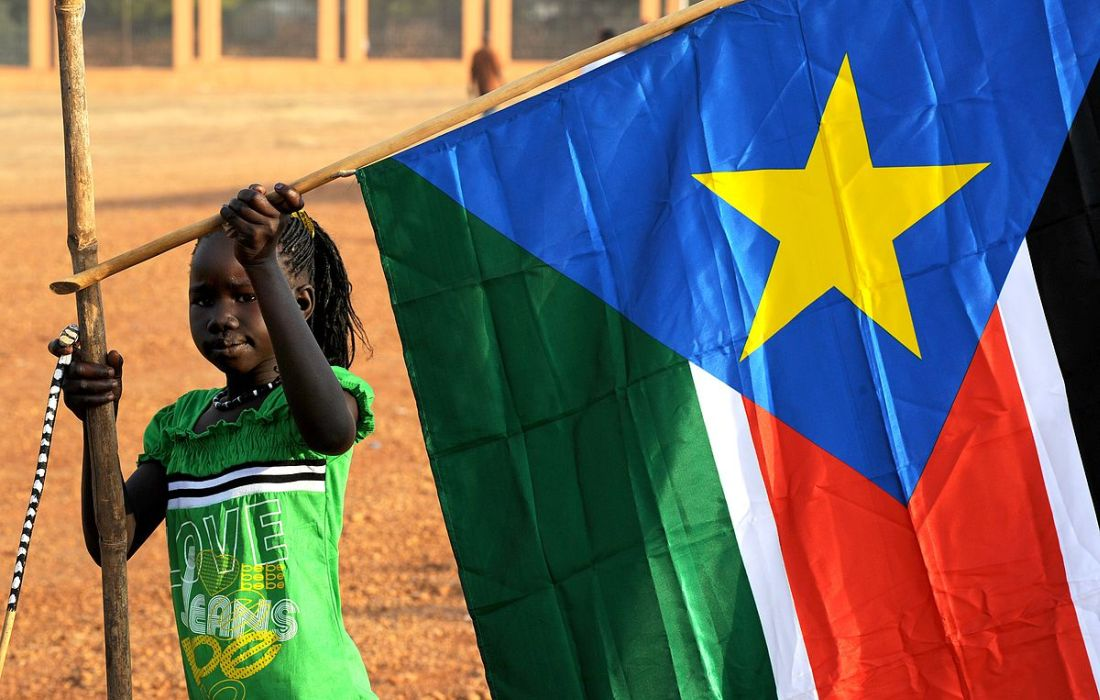 1200px-A_young_girl_hangs_the_South_Sudan_flag_(5925619011)