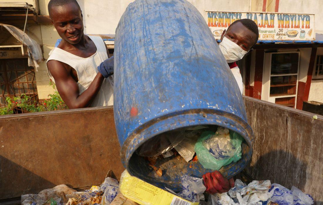 Trash Recycling Project in Bo/Sierra Leone: Fahrer: Alie Lamarsh (22), Assistent: Junisa Bangura (18, Mundschutz). Die beiden gehoeren zur Kissy Town Youth. Die Welthungerhilfe organisiert in Bo zusammen mit der Stadtverwaltung eine Muellabfuhr. Mit den Tricycles fahren Jugendliche von Haushalt zu Haushalt und holen den Muell ab. Flaschen, Plastiktueten und Dosen werden recycelt. Sierre Leone, trash recycling project in Bo, Alie Lamarsh, 22 years, assistant Junisa Bangura, 18 years, with breathing protector. Both belong to Kissy Town Youth. Welthungerhilfe organizes waste collection together with urban administration. Riding tricycles the youngsters fetch the waste from household to household. Bottles, plastic bags and tins are recycled.