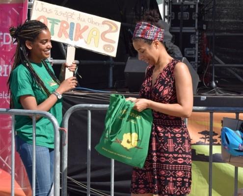 Scene vom KENAKO Festival 2018 in Berlin. Eine Mitarbeiterin macht mit einem Plakat auf das Bühnenquiz aufmerksam.