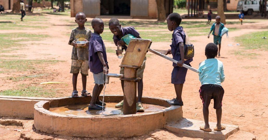 Kinder trinken Wasser aus einem Brunnen._©GEMEINSAM FÜR AFRIKA