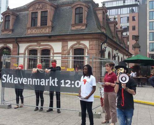 """Sklavenmarkt in Frankfurt. Drei """"Sklav*innen"""" im Käfig. ©GEMEINSAM-FUER-AFRIKA"""