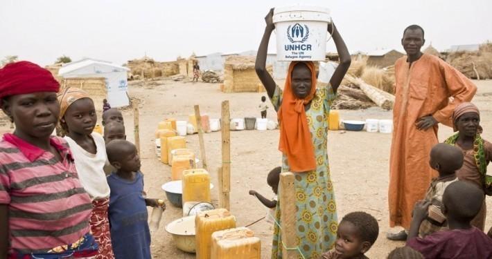 Ein Flüchtlingsmädchen trägt einen Eimer Wasser auf dem Kopf_©UNHCR/Helene Caux