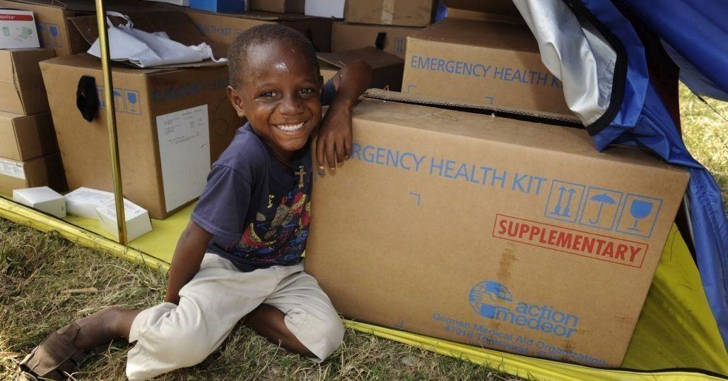 Ein kleiner Junge sitzt vor einer Lieferung von action medeor_©action medeor