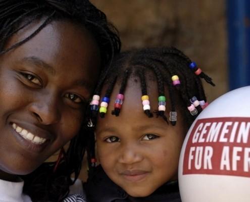 Eine Frau mit ihrem Kind und einem Luftballon in Kenia_©Gemeinsam für Afrika