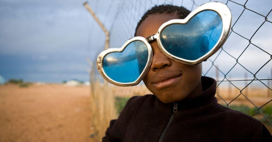 Eine Flüchtlingskind mit selbstgebastelter Herzbrille im Camp Osire, Angola. Eine Flüchtlingskind mit selbstgebastelter Herzbrille im Camp Osire, Angola._©UNHCR / Brandon Bannon