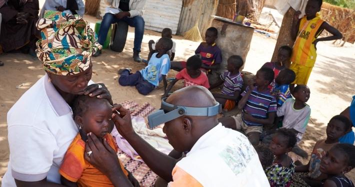 Optiker untersucht kleines Kind auf Trachome (Senegal)